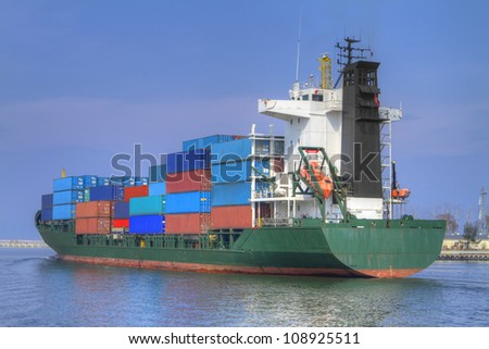 Huge container cargo ship heading for port - stock photo