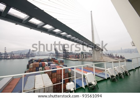Huge Container Ship entering port of Hong Kong, passing under the Stonecutters Bridge - stock photo