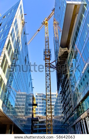 Huge crane rising between two buildings under construction - stock photo
