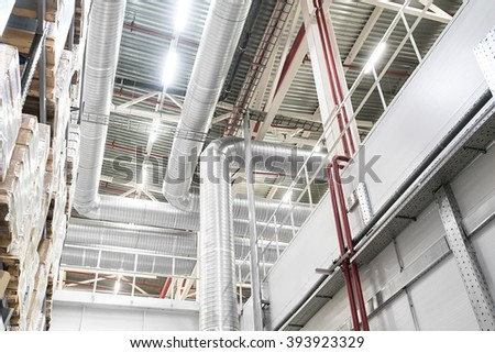 Huge distribution warehouse with high shelves and big ventilation pipes on the ceiling. Bottom view.