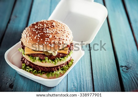 Huge double American cheeseburger with juicy beef patties on a sesame bun served in a disposable container as a delicious lunchtime snack on a rustic green table outdoors - stock photo