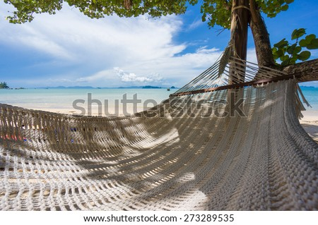 Huge empty hammock under palm tree at the ocean beach in sunny day - stock photo