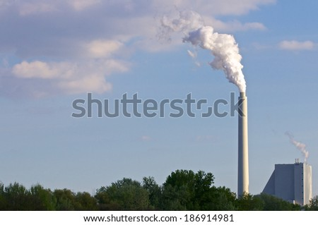 Huge factory chimney polluting the air - stock photo