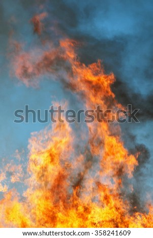 Huge flame against the blue sky during late day.