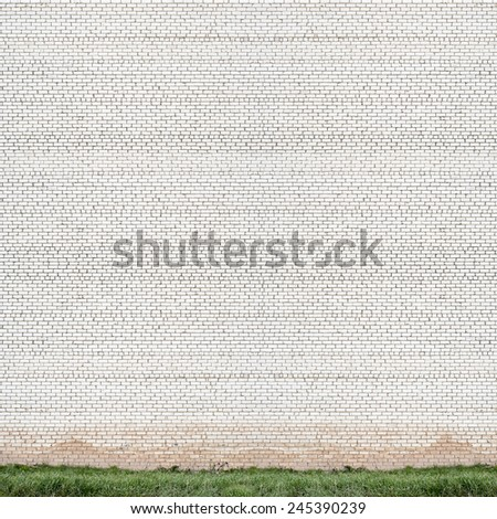 huge grunge white brick wall and green grass background - stock photo