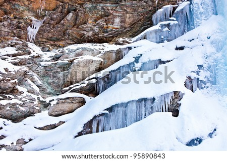 Huge icicles formed in a waterfall on a mountain - stock photo