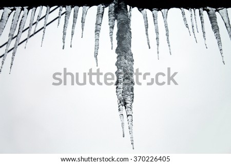 Huge icicles on the roof in Siberia winter - view from the window (Russia)
