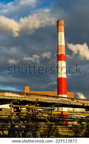 Huge industrial factory chimney in red and white rising high above towards a blue sky produces vast plumes of smoke or pollution into the environment - stock photo