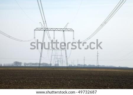 Huge, 750KV power line going through the fields - stock photo
