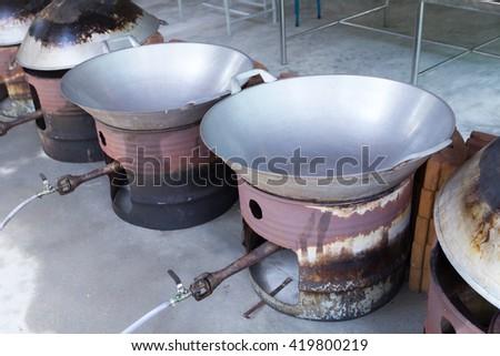 Huge metal pan in fried durian factory. - stock photo