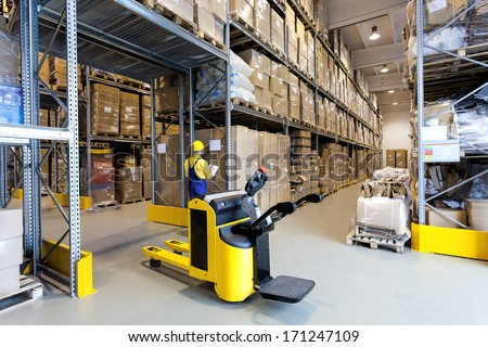 Huge metal stillage and yellow hand pallet truck in warehouse - stock photo