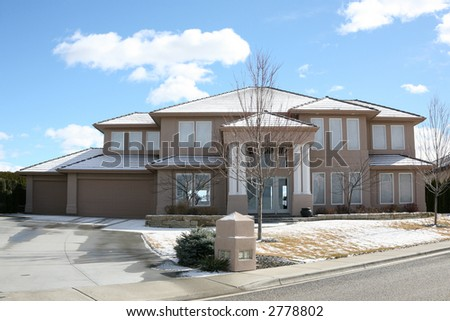 Huge modern house with snow and bright blue sky with clouds - stock photo