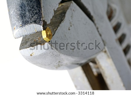 Huge monkey-wrench with a very small nut. - stock photo