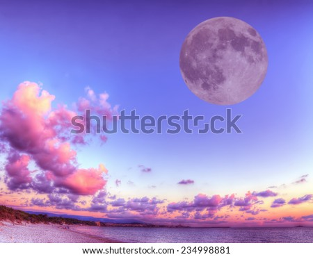 huge moon over a pink shore at sunset. Processed for hdr tone mapping effect. - stock photo
