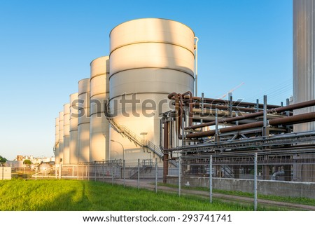 Huge oil tanks from the oil mill in the harbor of Hamburg. Storage tanks with soy oil in the industrial area of Hamburg. The company is one of the biggest for vegetable oil in Germany - stock photo