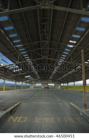 Huge old factory or industrial space with clouds and landscapes visible through all the openings - stock photo