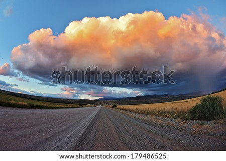 Huge pink - orange cloud, like a bowl of cream, lit the last rays of sunset. Gravel road through the Patagonian steppe
