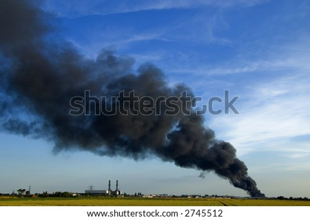 Huge plume of black smoke from fire rising high above flat land against blue sky - stock photo