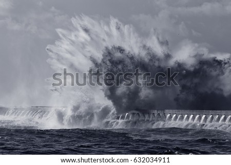 Huge sea wave splash toned blue. New pier of Douro river mouth, Porto, Portugal