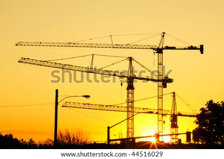 Huge sky cranes at a construction site silhouetted against a setting sun.