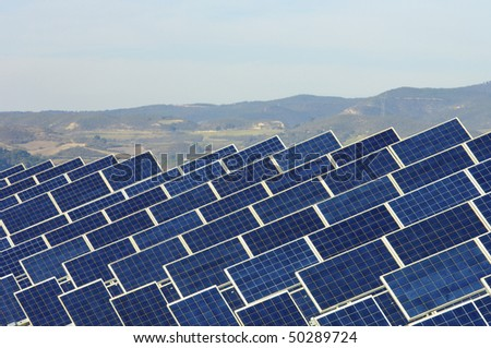 huge solar field with blue sky - stock photo