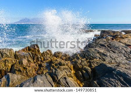 Huge splash over the rock - stock photo