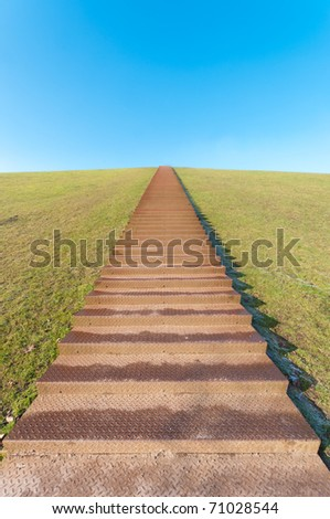 huge stairway leading to the top of a green hill - stock photo