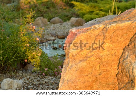 Huge stone and decorative garden pond at sunset - stock photo