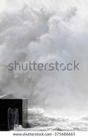 Huge stormy wave splash over a pier