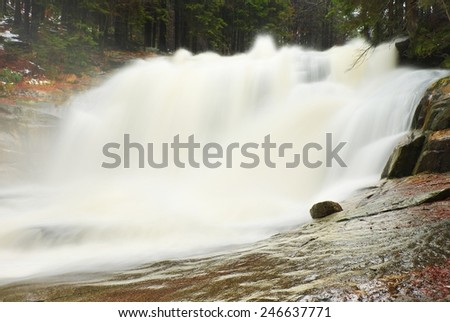 Huge stream of water is falling into foamy pond below. High cascade in forest. Crystal freeze water of mountain river. - stock photo