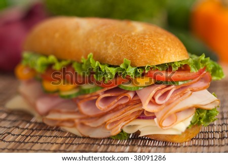 Huge submarine sandwich with turkey, ham & cheese, topped with lettuce, tomatoes, cucumbers - stock photo