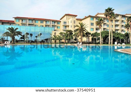 Huge swimming pool with tropical coconut trees and luxurious resorts in the background. Suitable for concepts such as business and executive travel, tourism, vacation and holiday, and relaxation.