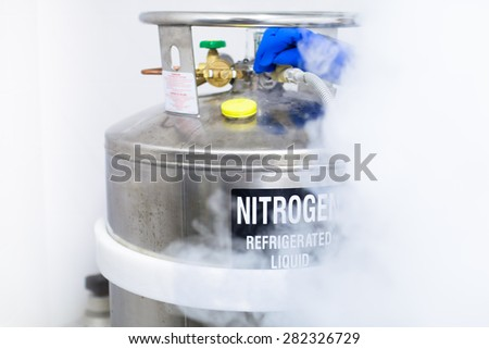 Huge tank of nitrogen half covered by fume caused by evaporation - stock photo