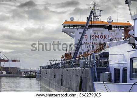 Huge Tanker is being refueled with Heavy oil fuel (HFO) by a bunker barge. Cloudy sky above the container terminal at the background. - stock photo