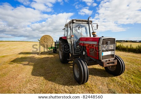 huge tractor collecting a roll of haystack in the field at nice blue sunny day - stock photo