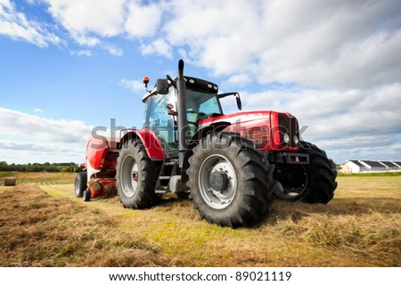 huge tractor collecting haystack in the field at nice blue sunny day - stock photo