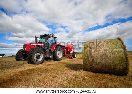huge tractor collecting haystack in the field in a nice blue sunny day - stock photo