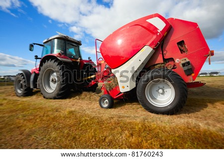huge tractor collecting haystack in the field in a nice blue sunny day, panning technique - stock photo