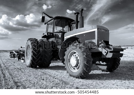 Huge tractor on the agricultural field on sunny summer day.