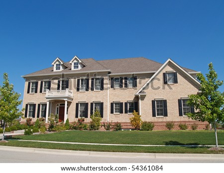 Huge two story brick home with black shutters. - stock photo