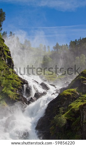 huge waterfalls in norway with woods, mountains and blue sky