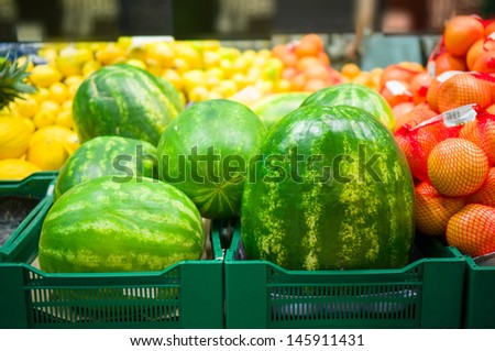 Huge watermelons, grapefruits and pineapples on boxes in supermarket - stock photo