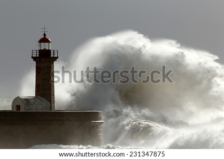 Huge wave over old lighthouse of Porto, Portugal. Low edition photo. - stock photo