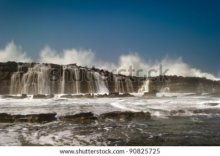 huge wave splashing on rocks wall and become waterfalls - stock photo