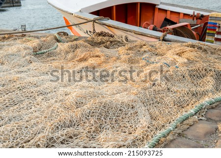 Huge white fishing net spread on the ground with a small boat on the second plan tied to the shore - stock photo