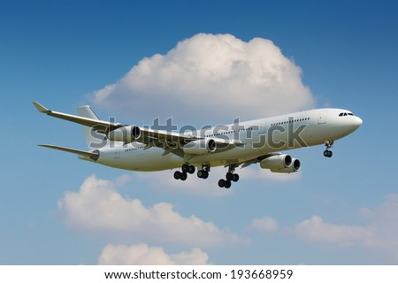 Huge white plane with four engines on final approach - stock photo
