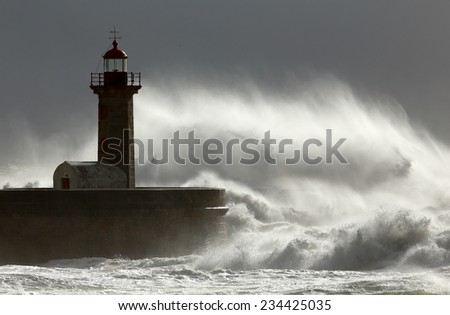 Huge windy wave against lighthouse  - stock photo