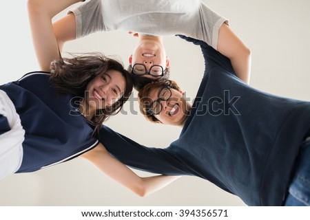 Hugging Asian friends standing in circle and smiling ta camera, view from below - stock photo