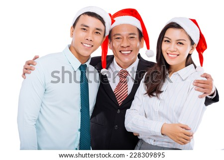 Hugging business team in Santa Claus hats - stock photo