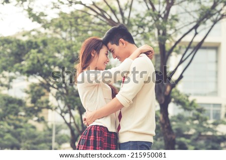 Hugging couple smiling and looking at each other, side view - stock photo